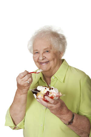 A beautiful elderly Caucasian woman eating a banana split icecream