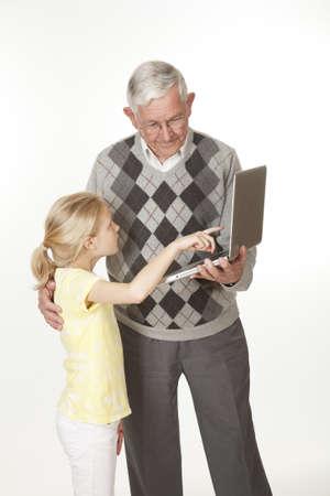 コンピューターに何か彼女の祖父を示すかわいい白人孫娘