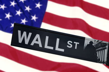 currency exchange: Wall street sign in front of the United States Flag