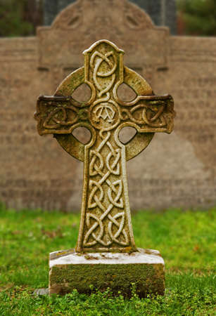 Celtic cross at a gravesite in an old cemetery photo