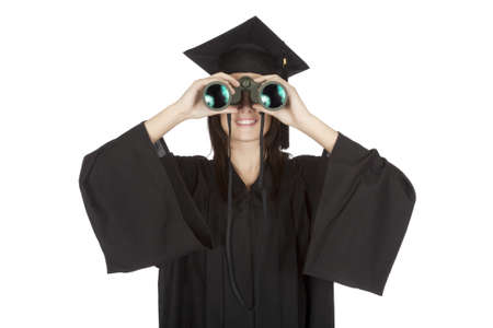 Beautiful Caucasian woman wearing in a black graduation gown and looking through binoculars photo