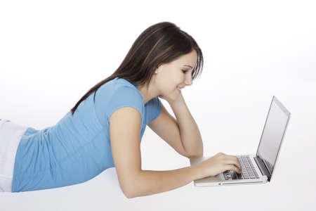 Attractive young girl using notebook computer on white background. Stock Photo - 9673647