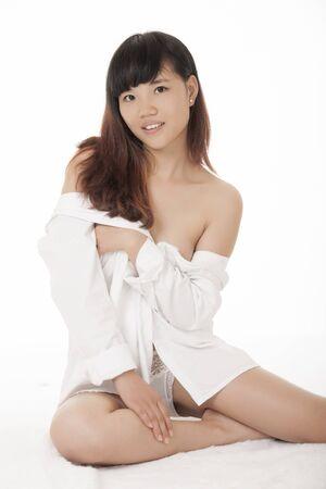 Bella donna cinese che indossa una camicia bianca isolato su uno sfondo bianco