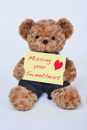 A cute teddy bear holding a yellow sign that says Missing my sweetheart isolated on a white