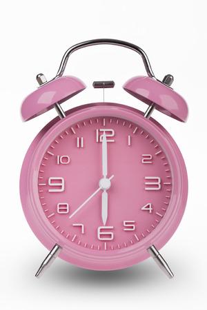 Roze wekker met de handen om 6 uur of uur geïsoleerd op een witte achtergrond. Stockfoto