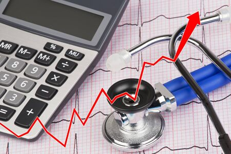 Close up of a graph with an Electrocardiograph also known as a EKG or ECG graph with a stethoscope and calculator showing the high cost of health care Stock Photo