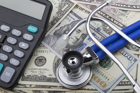 USD bank notes with a stethoscope and calculator showing the high cost of health care Stock Photo