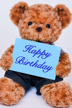 cute teddy bear holding a blue sign that reads happy birthday