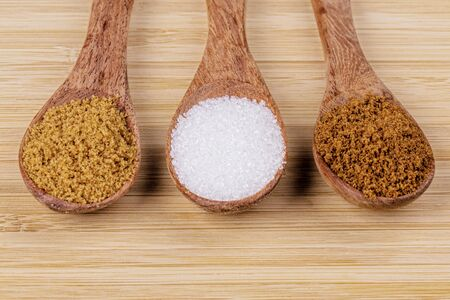 Three wooden spoonfull of different sugars, light brown sugar, dark brown sugar, and granulated sugar on a wooden background