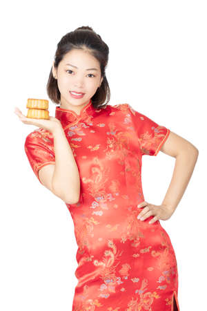 Beautiful Chinese woman wearing a Cheongsam or Chipao holding a Moon Cake the traditional food of the Chinese holiday of Mid Autumn Festival isolated on a white background