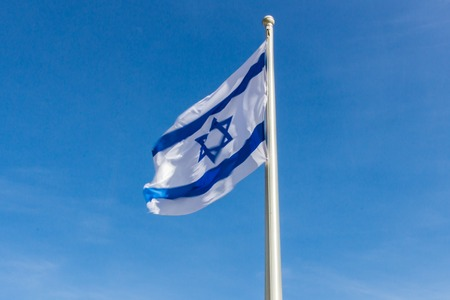 flapping: Israel flag flapping in the wind.the flag is flapping and there are blue clouds behind it. Stock Photo