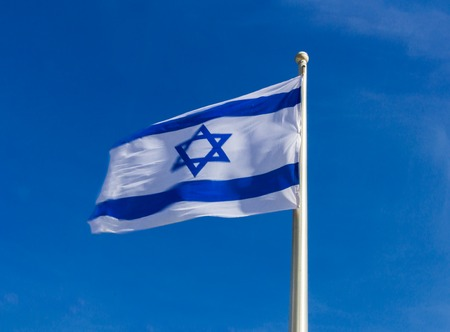 Israel flag flapping in the wind.the flag is flapping and there are blue clouds behind it. Reklamní fotografie