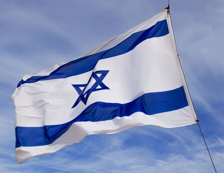 zion: Israel flag flaping in the wind.the flag is flapping and there are blue clouds behind it.