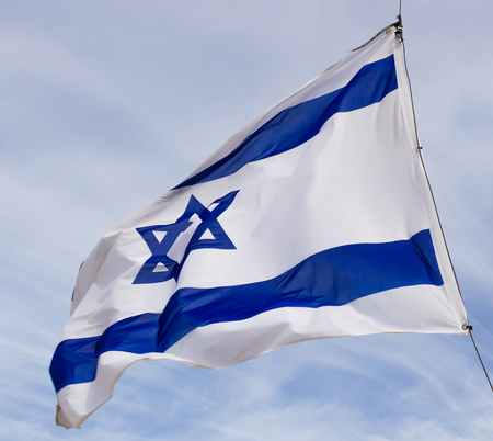 Israel flag flaping in the wind.the flag is flapping and there are blue clouds behind it.