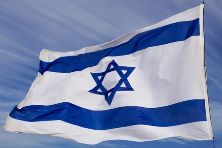 flapping: Israel flag flaping in the wind.the flag is flapping and there are blue clouds behind it.