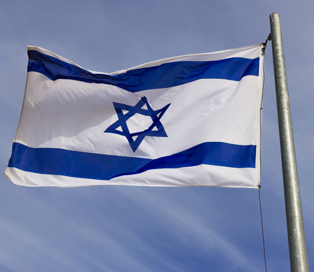 zion: Israel flag flapping in the wind.the flag is flapping and there are blue clouds behind it. Stock Photo