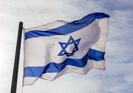 flag pole: Israel flag flaping in the wind.the flag is flapping and there are blue clouds behind it.