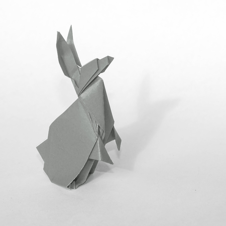 pointy ears: Gray Origami rabbit made of colored paper. the rabbit is standing on a white surface and casts shadow.  It has long pointy ears.