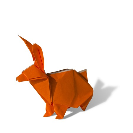 Origami rabbit made of colored paper. the rabbit is standing on a white surface and casts shadow.  It has long pointy ears. photo