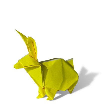 Origami rabbit made of colored paper. the rabbit is standing on a white surface and casts shadow.It has long pointy ears. photo