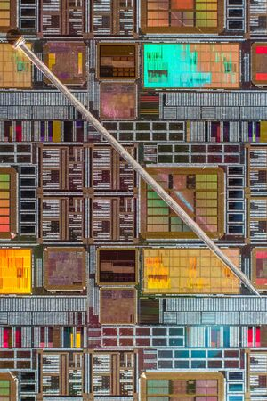 compared: Silicon wafer with printed electronic circuit compared to a needle