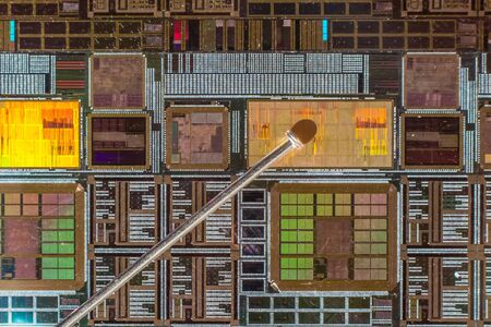 Silicon wafer with printed electronic circuit compared to a needle photo