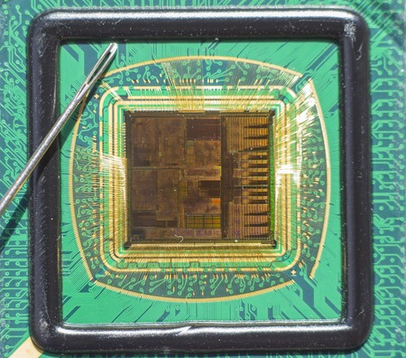 compared: Open computer chip with gold wire connections compared to a needle