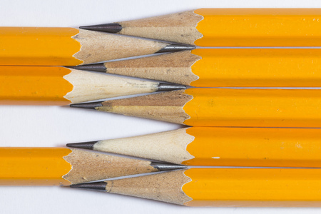 A group of pencils isolated on white. The pencils tips are nearly touching each other.  This is a macro image.