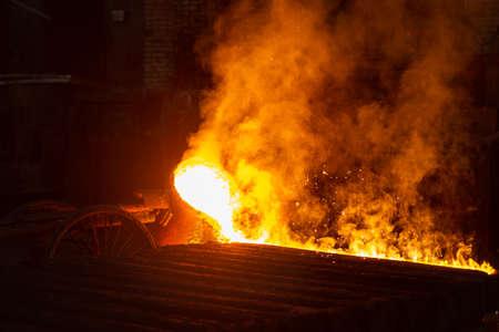 Le métal chaud est versé du bol dans une forme spéciale dans une aciérie