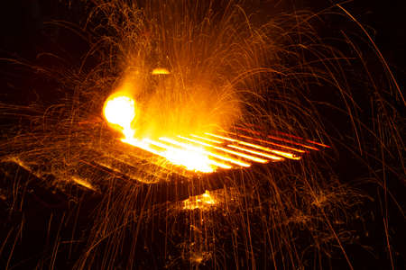 Hot steel casting in a factory with bright flashing sparks