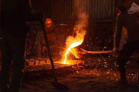 Men work with hot metal casting it in a special form Фото со стока