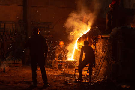 Men work with hot metal casting it in a special form. Hot metal is poured from the bowl into a special form in a steel factory