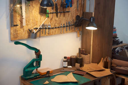 A small business of a craftsman making leather products and goods. Set of craft tools for leather work on the leatherman work desk. Tools for craft production of leather goods on wooden table.