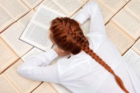Closing schools and universities. Distance learning. Student girl tired of quarantine and self-isolation. A red-haired girl lies among many books.