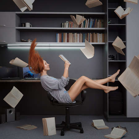Redhead girl reading flying books in chair in a room. Fantasy photo of a girl levitates in a room full of flying books.