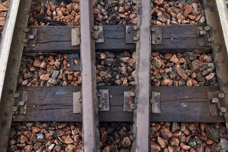 Close-up of old rusty steel rails, sleepers and gravel. Oiled sleepers near the railway station. Rails section on the railway. With sleepers on rubble.
