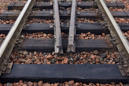 Close-up of old rusty steel rails, sleepers and gravel. Oiled sleepers near the station. Rails section on the railway. With sleepers on rubble. Standard-Bild
