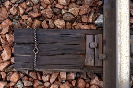Detail of rusty screws on railroad track. Wooden tie with rusty nuts and bolts. Single rail as part of a railway. Close up of old abandoned rusty rails with wooden sleepers.