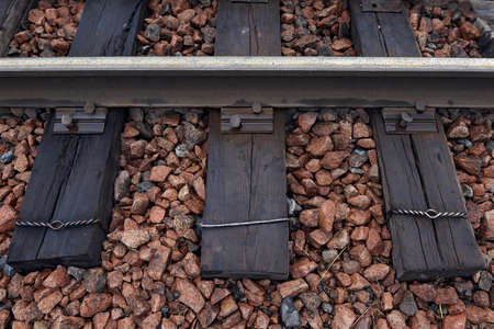 Old rusty steel rails and sleepers on rubble