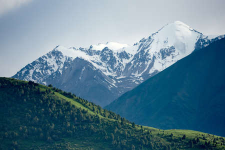 The nature of Kyrgyzstan. Summer. Mountain landscape. Among green valleys, mountains are visible at middle of the day. Tien Shan Mountains, Kyrgyzstan.