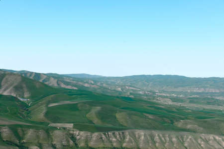 The nature of Kyrgyzstan. Summer. Mountain landscape. Among green valleys, mountains are visible at middle of the day