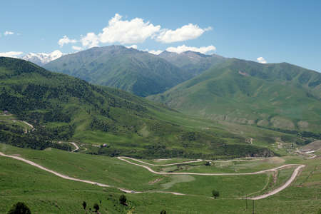 The nature of Kyrgyzstan. Country road across mountains. Mountain landscape. Among green valleys, mountains are visible at middle of the day. Standard-Bild