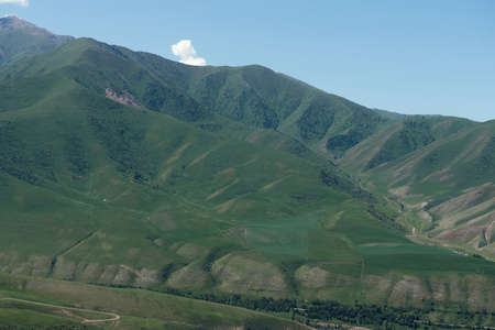 The nature of Kyrgyzstan. Summer. Mountain landscape. Among green valleys, mountains are visible at middle of the day.