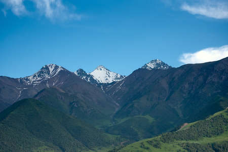 Mountain landscape of Kyrgyzstan. Among green valleys, mountains are visible at middle of the day. Tien Shan Mountains, Kyrgyzstan. Standard-Bild