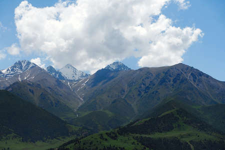 The nature of Kyrgyzstan. Mountain landscape. Among green valleys, mountains are visible at middle of the day. Tien Shan Mountains, Kyrgyzstan.