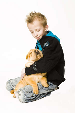 k9: Young boy holding a sleeping sharpei puppy Stock Photo