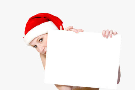 Beautifull girl in christmas bikini and with christmas hat is holding up a white sign for copy space. photo