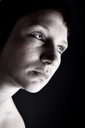 Studio portrait of a young woman with short hair looking mysterious photo