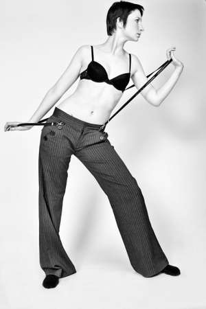 studioshot: Studio fashion portrait of a young woman with short hair posing fashinably in bra and trousers Stock Photo