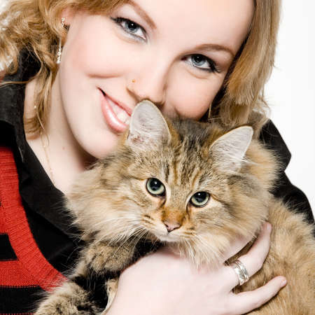 Studio portrait of a young blond curly woman holding a cute main coone kitten Stock Photo - 2318957